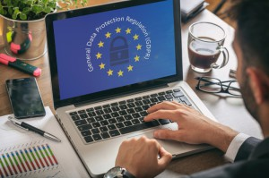 Man working on laptop with GDPR and EU symbols superimposed